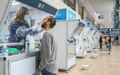 A technician collects nasal swab samples for COVID-19 at the coronavirus lab, at Ben-Gurion International Airport on December 14, 2020. (Yossi Aloni/Flash90)
