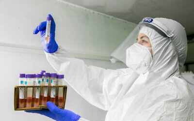 A Maccabi health care worker carries coronavirus test samples in Rehovot on December 15, 2020. (Yossi Aloni/Flash90)