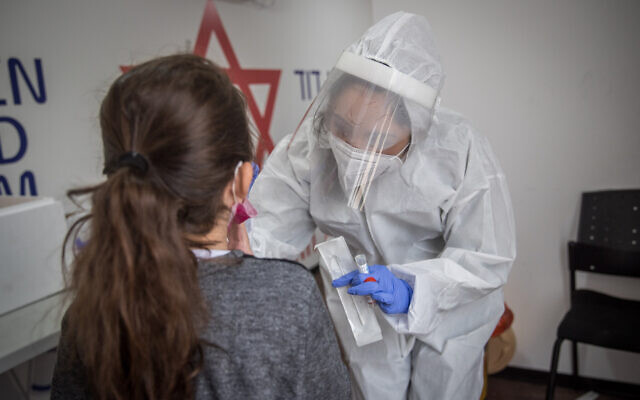 A Magen David Adom medical worker test Israelis for coronavirus at a mobile testing site in Jerusalem on December 16, 2020. (Yonatan Sindel/Flash90)