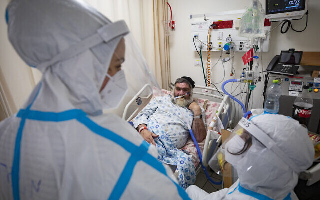 A COVID-19 patient hospitalized at  the Shaare Zedek hospital Coronavirus ward receives a visit from his two daughters in Jerusalem on December 17, 2020. (Olivier Fitoussi/Flash90)