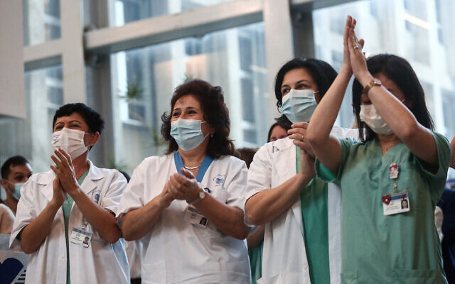 Israeli medical workers cheer at Tel Aviv Sourasky Medical Center (Ichilov), on December 20, 2020 as the country's vaccination drive begins (Miriam Alster/Flash90)
