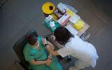 An Israeli medical worker receives a COVID-19 vaccine at Ichilov Hospital in Tel Aviv on December 20, 2020. (Miriam Alster/Flash90)