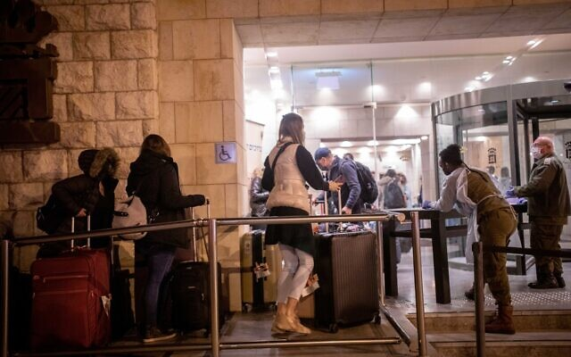 People who landed on a flight from England arrive at the Dan Panorama Hotel in Jerusalem, which is being used as a quarantine facility, on December 20, 2020. (Yonatan Sindel/Flash90)