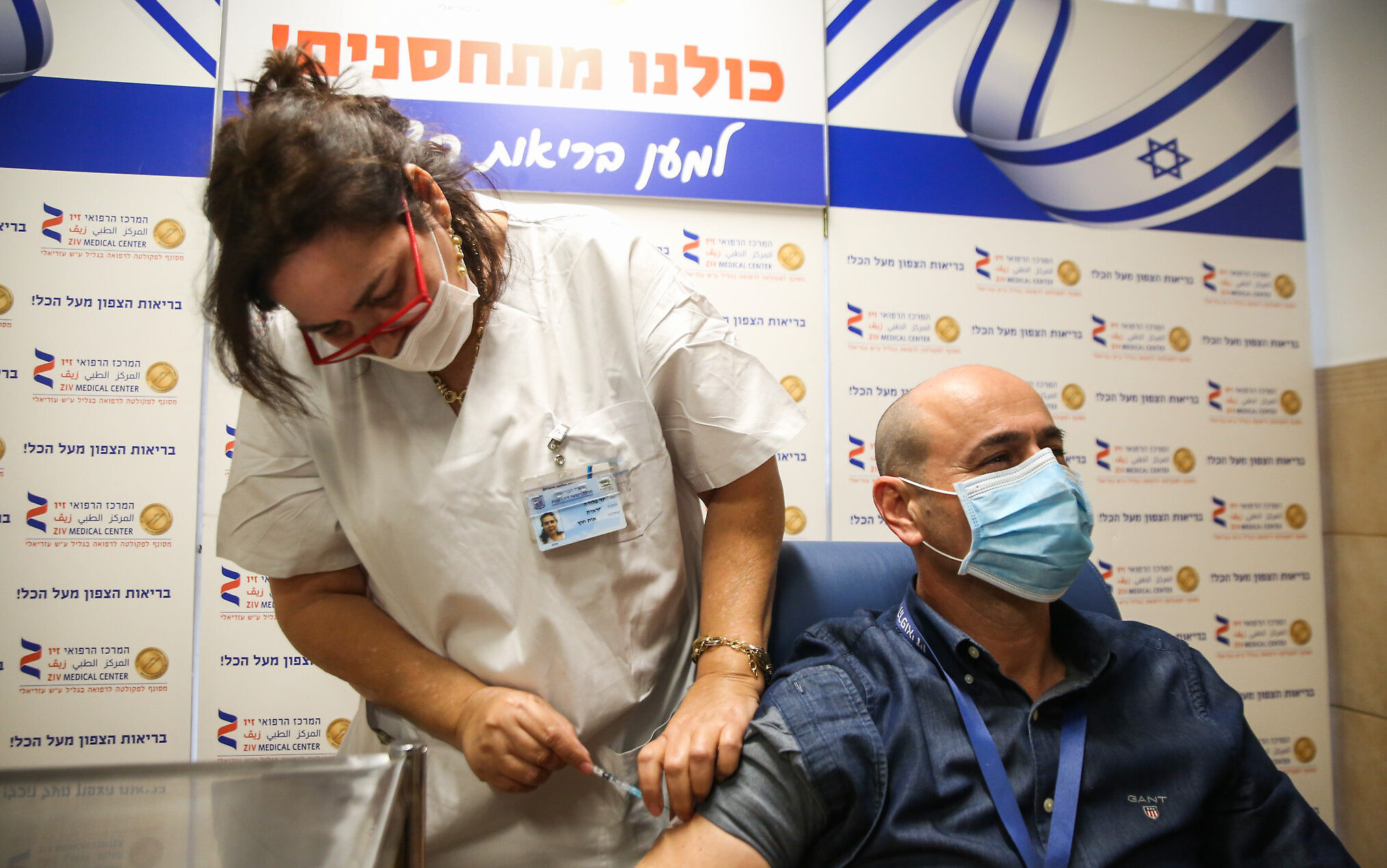 A medical worker receives a COVID-19 vaccine at Ziv Medical Center in the northern city of Safed, December 21, 2020. (David Cohen/Flash90)