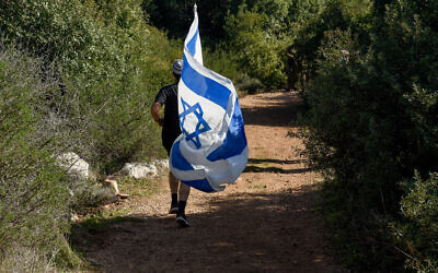 A person runs with an Israeli flag in the Reihan forest near Tal Menashe in the West Bank where Esther Horgen was found dead in suspected terror attack, Dec. 21, 2020. (Flash 90/Meir Vaknin)