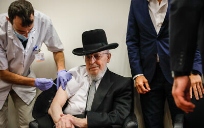 An Israeli citizen receives a COVID-19 vaccine, at a Meuhedet vaccination center in Jerusalem, on December 21, 2020. (Olivier Fitoussi/Flash90)