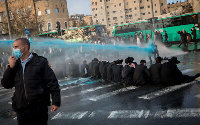 Ultra-Orthodox Jews in Jerusalem clash with police as they protest against the arrest of a draft-dodging yeshiva student, December 22, 2020. (Yonatan Sindel/Flash90)
