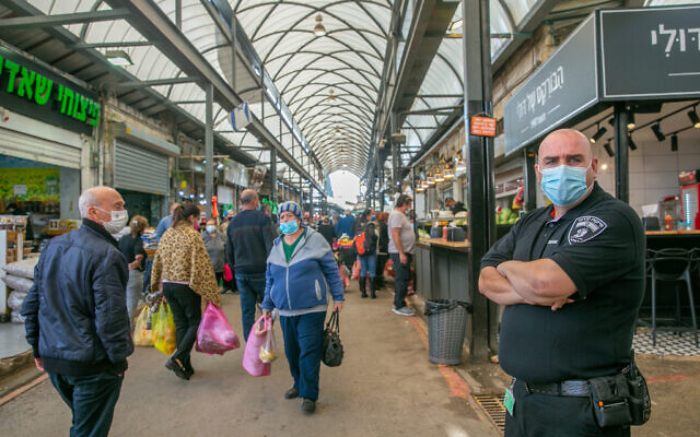 Israelis shop at the market in Ramle. The market has been partially closed down due to restrictions to prevent the spread of the coronavirus. December 23, 2020. (Yossi Aloni/FLASH90)