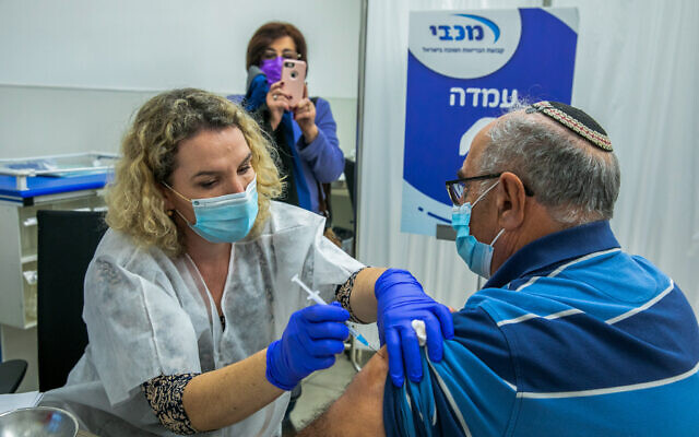 A man receives a COVID-19 vaccine at Maccabi Healthcare Services vaccination center in Modiin, on December 24, 2020. (Yossi Aloni/Flash90)