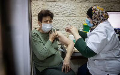 A woman receives a COVID-19 vaccine at a Clalit clinic in Jerusalem on December 24, 2020. (Yonatan Sindel/Flash90)