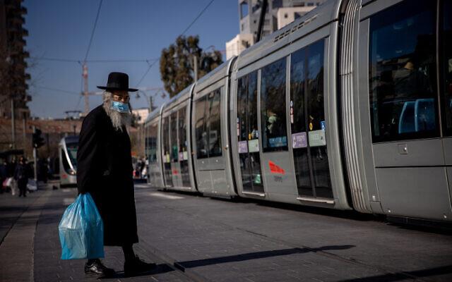 A man wearing a face mask near the Mahane Yehuda market in Jerusalem on December 25, 2020. (Yonatan Sindel/Flash90)
