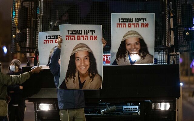 Demonstrators holds placards showing Ahuvia Sandak as they protest against his death in a car crash during a police chase last week, outside the national police headquarters in Jerusalem, on December 26, 2020. (Yonatan Sindel/Flash90)