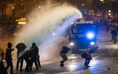 Police officers clash with demonstrators during a protest following the death of Ahuvia Sandak during a police chase, outside the police headquarters in Jerusalem, December 26, 2020 (Yonatan Sindel/Flash90)