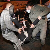 Police clash with ultra-Orthodox Jews protesting the arrest of a draft dodger, in the central city of Bnei Brak, December 27, 2020. (Noam Revkin Fenton/Flash90)