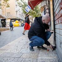 A man closes his shop in Jerusalem on December 27, 2020, as Israel enters its 3rd nationwide lockdown. (Yonatan Sindel/Flash90)