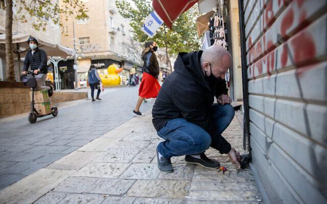 A man closes his shop in Jerusalem on December 27, 2020, as Israel enters its 3rd nationwide lockdown. (Yonatan Sindel/Flash90)