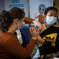 A woman receives a COVID-19 vaccine in Jerusalem on December 28, 2020. (Yonatan Sindel/Flash90)