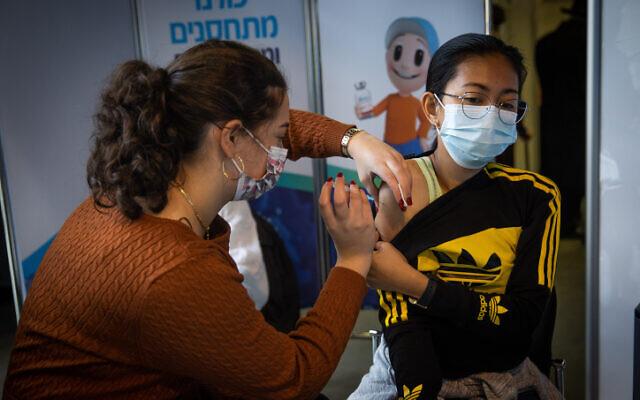A woman receives a COVID-19 vaccine in Jerusalem on December 28, 2020. (Yonatan Sindel/Flash90)