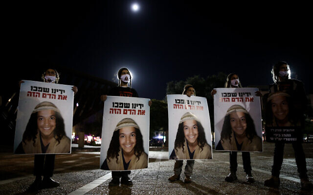 Demonstrators holds placards showing Ahuvia Sandak as they protest against his death in a car crash during a police chase last week, at Rabin Square in Tel Aviv on December 29, 2020. (Miriam Alster/Flash90)
