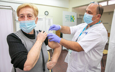 A woman receives a COVID-19 vaccine at a Clalit vaccination center in Rehovot on December 29, 2020. (Yossi Aloni/Flash90)