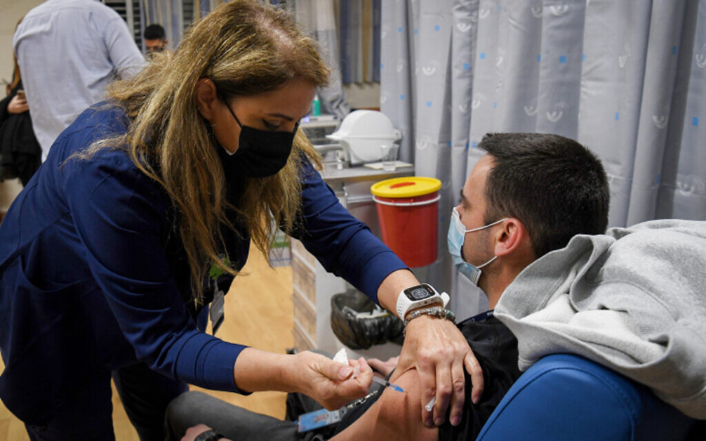 An Israeli teacher receives a COVID-19 vaccine, at the Shamir Medical Center in Be'er Ya'akov, on December 30, 2020. (Avi Dishi/Flash90)
