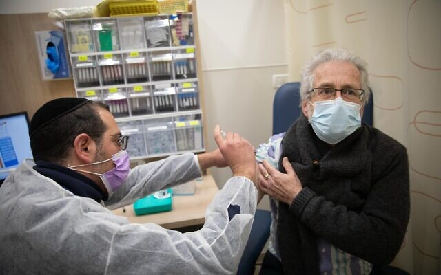 A man receives a COVID-19 vaccine, at a vaccination center in Jerusalem, on December 30, 2020. (Noam Revkin Fenton/Flash90)