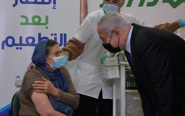 Prime Minister Benjamin Netanyahu visits a vaccination center in Tira on December 31, 2020 (Amos Ben Gershom/GPO)