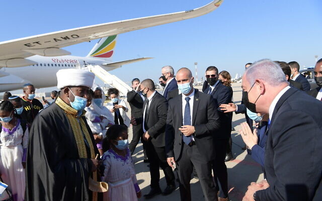 Prime Minister Benjamin Netanyahu, right, greets members of the Ethiopian Jewish community as they arrive at  Ben Gurion airport, outside Tel Aviv, on December 3, 2020. (Amos Ben Gershon/GPO)