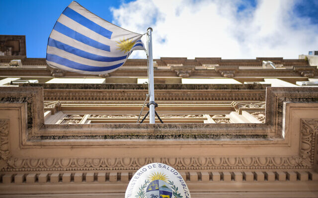 Uruguayan flag flies in front of the entrance to the Ministry of Public Health as precautions are taken against COVID-19 in Montevideo, Uruguay on March 16, 2020. (Carlos Lebrato/Anadolu Agency/Getty Images via JTA)