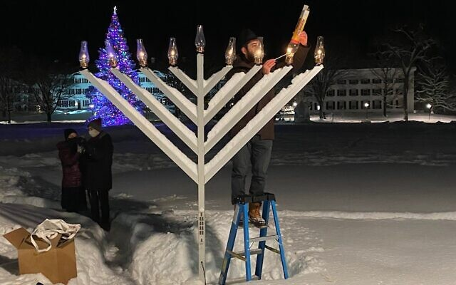 Rabbi Moshe Gray lights the Dartmouth campus menorah the night after he discovered that it had been shot through with a pellet gun. The menorah can still be lit with fire despite the vandalism. (Courtesy of Gray via JTA)