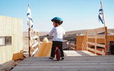 A younger resident of Shahak Heights enjoying his bike. (Shira Malul/via Ayalim)