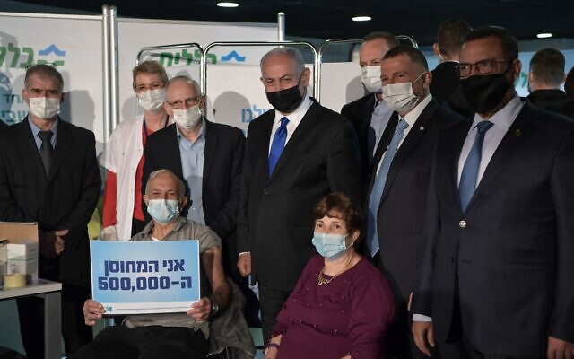 Prime Minister Benjamin Netanyahu (4L) and Health Minister Yuli Edelstein (2L) accompany David Herzl Levy as he becomes the 500,000th Israeli to receive a coronavirus vaccine.(Amos Ben-Gershom/GPO)