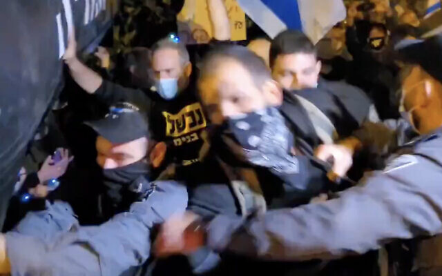 Anti-Netanyahu protesters scuffle with police during a demonstration in the northern town of Binyamina, on December 31, 2020. (Screen capture: Twitter)