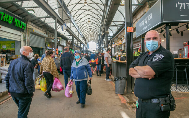 Israelis shop at the market in Ramle, central Israel, that is partially closed due to coronavirus restrictions, December 23, 2020. (Yossi Aloni/Flash90)