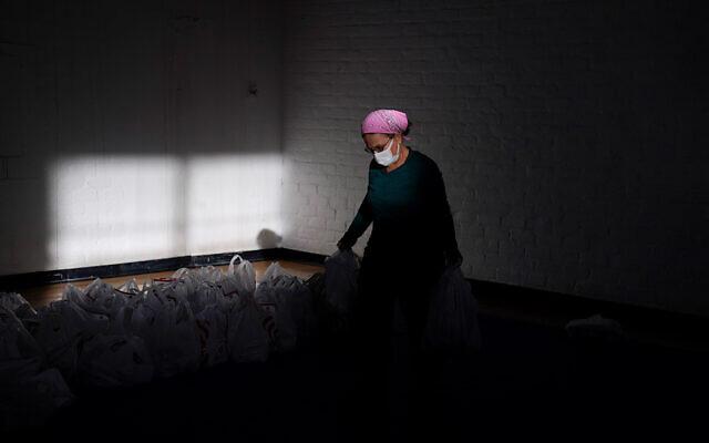 A volunteer prepares supplies for a food bank in Los Angeles, California, December 17, 2020. (AP Photo/Jae C. Hong)
