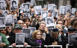 Mourners hold up pictures of people who died in the bombing of the AMIA Jewish center that killed 85 people on the 25th anniversary of the attack in Buenos Aires, Argentina, July 18, 2019. (AP Photo/Natacha Pisarenko)