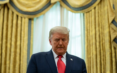 US President Donald Trump listens during a ceremony to present the Presidential Medal of Freedom to former football coach Lou Holtz, in the Oval Office of the White House, December 3, 2020. (AP Photo/Evan Vucci)