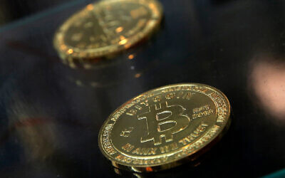 Illustrative: Coins are displayed next to a Bitcoin ATM in Hong Kong, December 8, 2017. (AP Photo/Kin Cheung, File)