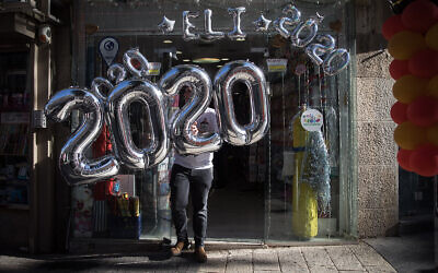 Celebratory 2020 balloons are hung from a storefront in Jerusalem on New Year's Eve, December 31, 2019. (Hadas Parush/Flash90)