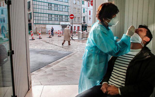 A pharmacist administers a nasal swab at a pharmacy in Bayonne, southwestern France, Dec.24, 2020. (AP/Bob Edme)