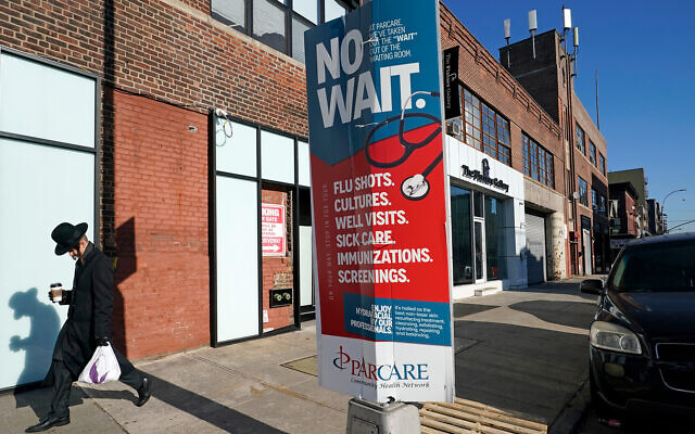 A man walks past a sign advertising the services of ParCare Community Health Care Network in front of the company's facility in the Williamsburg neighborhood of the Brooklyn borough of New York, December 27, 2020. (AP Photo/Kathy Willens)