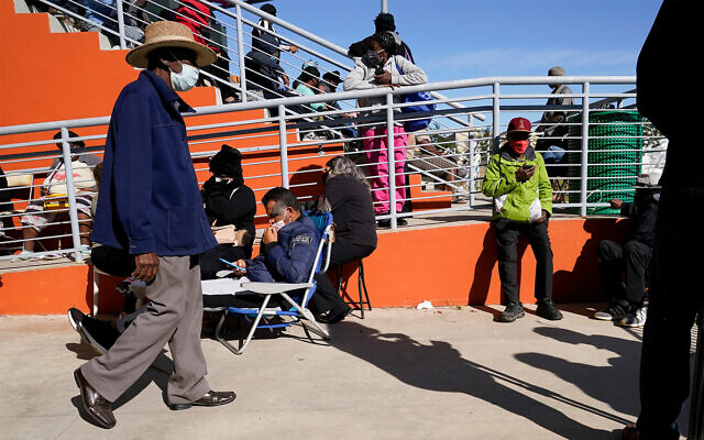 People wait for their numbers to be called for a place in line to receive a $250 grocery gift card available to Miami residents experiencing hardship and food insecurity due to COVID-19, in Miami, Florida, December 8, 2020. (AP Photo/Lynne Sladky)
