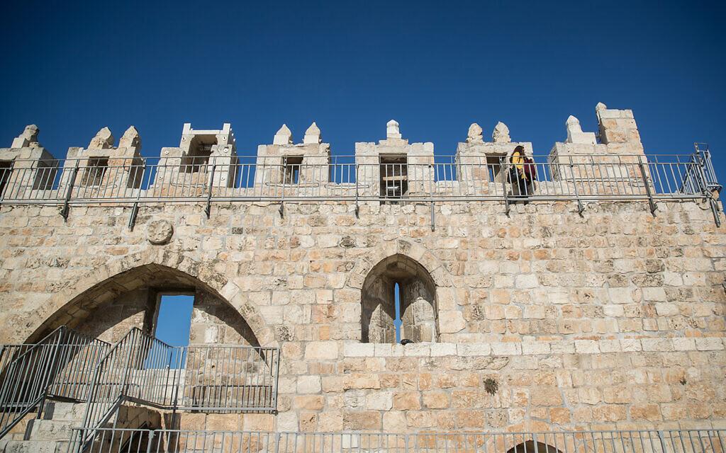 A visitor tours the Jerusalem Ramparts Walk on Jerusalem's Old City walls, on December 17, 2019. (Yonatan Sindel/Flash90)