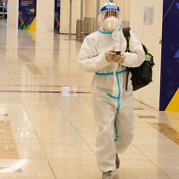 A passenger in a full, disposable hazmat suit arrives at the baggage claim area of Dubai International Airport's Terminal 3 in Dubai, United Arab Emirates, Nov. 26, 2020. (AP Photo/Jon Gambrell)