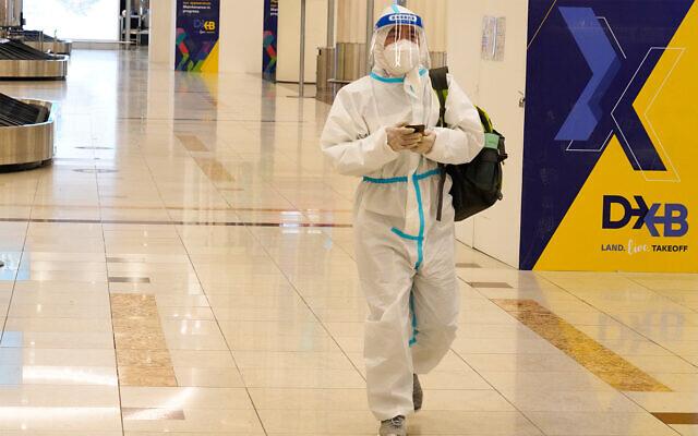 A passenger in a full, disposable hazmat suit arrives at the baggage claim area of Dubai International Airport's Terminal 3 in Dubai, United Arab Emirates, Nov. 26, 2020. (AP Photo/Jon Gambrell)