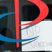 """A sign on the entrance to a Parcare health care facility announces that they have """"No Vaccines!!"""" in the Williamsburg section of Brooklyn, New York, December 27, 2020. (AP Photo/Kathy Willens)"""