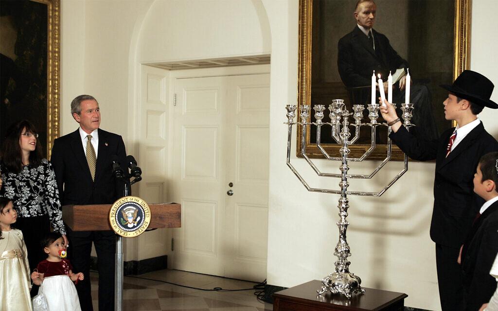 President George W. Bush looks on as 13-year-old Menachem Felzenberg, right, lights a menorah before the annual White House Hanukkah Reception on Thursday, Dec. 9, 2004 in Washington. (AP Photo/Evan Vucci)
