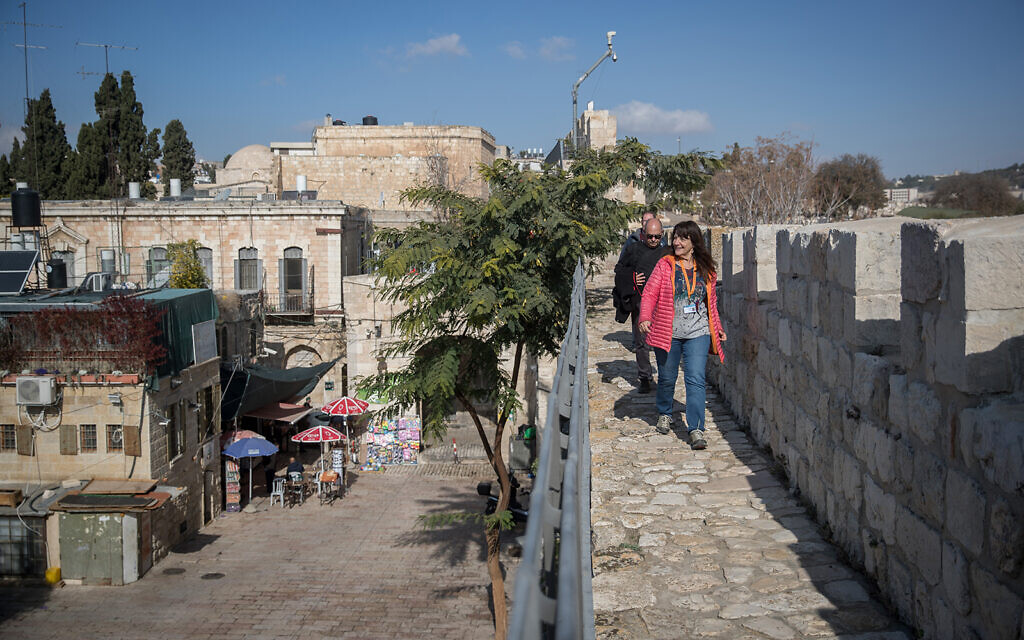 Visitors tour the Jerusalem Ramparts Walk on Jerusalem's Old City walls, on December 17, 2019. (Yonatan Sindel/Flash90)