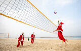 Four volleyball-playing Santa Clauses have a game on the Tel Aviv beach (Courtesy YoSee Gamzoo Letova/Tel Aviv Global & Tourism)