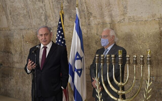 """Prime Minister Benjamin Netanyahu, left, and US Ambassador David Friedman at the Western Wall on December 10, 2020, the first night of Hanukkah. Netanyahu hailed the """"light"""" of US President Donald Trump's announcement that Morocco and Israel are to establish full relations, issued hours earlier. (Kobi Gideon/GPO)"""